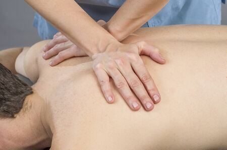 spinal adjustment: physiotherapist doing a back massage to man patient. Osteopathy. Stock Photo