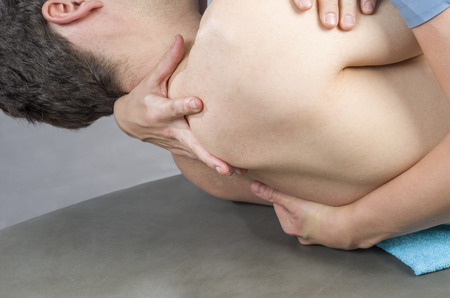 spinal adjustment: Physiotherapist doing manipulation to man patient. Osteopathy. Stock Photo