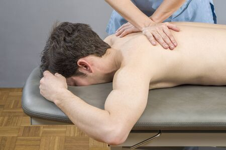 spinal adjustment: physiotherapistdoing a back massage to man patient. Osteopathy.