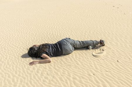 fainted: Woman fainted in desert sand. Stock Photo