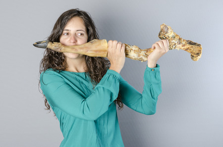 transverse: Crazy woman playing a transverse flute with leg ham finished. Make silly. Stock Photo