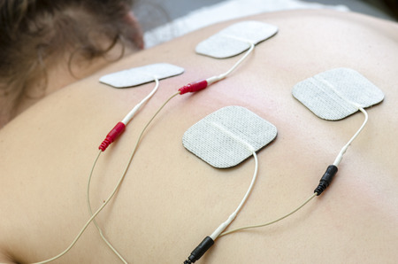 posture correction: TENS electrodes positioned for back pain treatment in physical therapy.