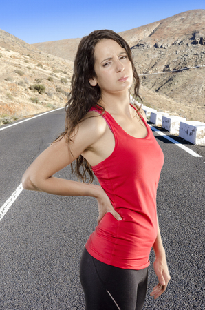 spinal disc herniation: Back pain. Athletic woman in red sportswear standing with her hand in her back.