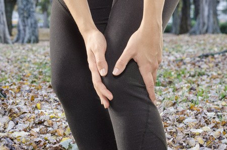 Injuries - sports running knee injury on woman. Woman runner with pain, maybe from sprain knee. Close up of legs outdoors.