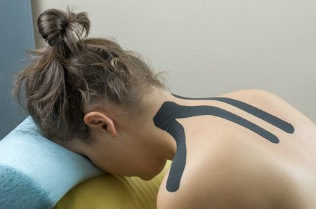 Physiotherapist putting on black kinesio tape on woman patients back.