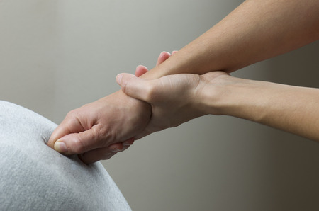 contracture: Chiropractor is doing a  office massage on chair.