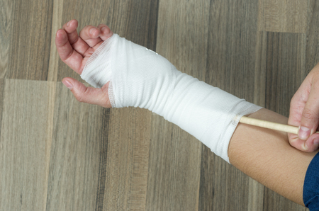 sprained: Woman scratching with a pen to injured wrist. Dont do it! is dangerous for yourself.