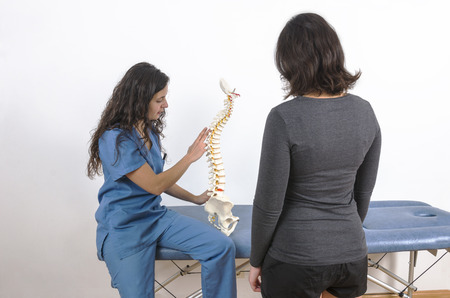 herniated: Doctor showing a skeleton to a patient. Back pain. Stock Photo