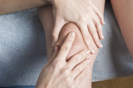 orthopaedic: Physiotherapist, chiropractor doing a patellar mobilization, Knee pain.