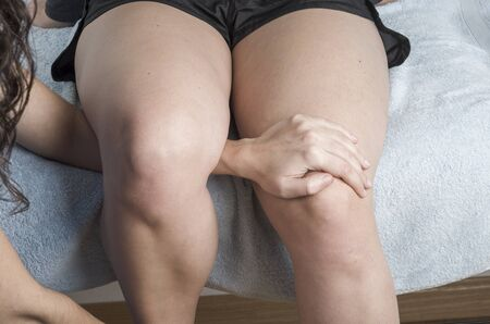 knees bent: Physiotherapist, chiropractor doing a passive physiological knee flexion. Stock Photo