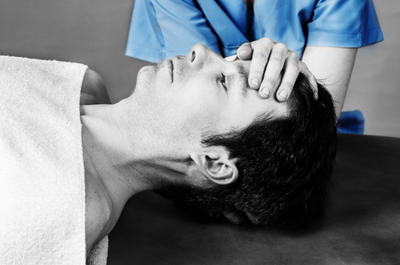 sacral: Physiotherapist doing a cranial sacral therapy to a man patient. Stock Photo