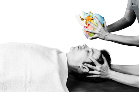 sacral: Physiotherapist doing a cranial sacral therapy to a man patient and another physiotherapist with a fake skull showing  position of the hands. Stock Photo