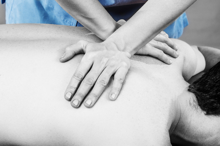 spinal adjustment: Physiotherapist doing a back massage to man patient in silhouette studio. Osteopathy.