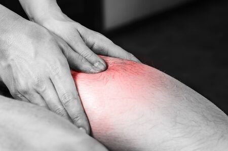 spinal adjustment: Closeup of hands of chiropractorphysiotherapist doing calf muscle massage to man patient,  in silhouette studio. Red color pain.