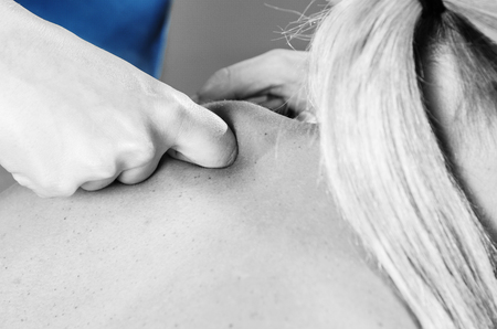 postural integration: Doctor, physiotherapist examining her patient back and doing decontracting massage in silhouette studio on white background.