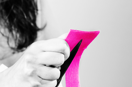 Closeup of physiotherapist  doctor is cutting pink kinesiotape in silhouette studio on white background.