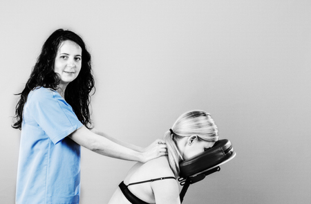 posture correction: Doctor, physiotherapist examining her patient back and doing decontracting massage in silhouette studio on white background.