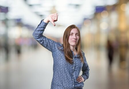 Pretty business woman making thumb down gesture over blur background.