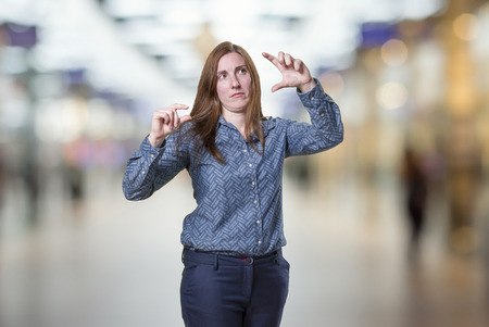 Pretty business woman doing tiny and big sign over blur background.