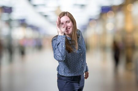 Pretty young business woman making a joke over blur background