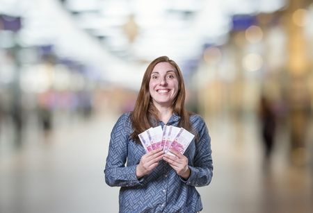 Pretty young happy business woman taking a lot of money over blur background.