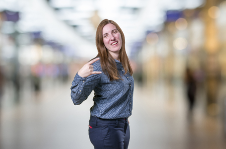 Pretty young business woman making horn gesture over blur background Stock Photo