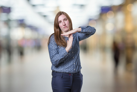 Pretty business woman making time out gesture oover blur background.