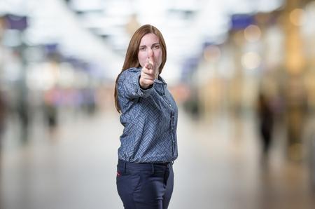 Pretty business woman making gun gesture over blur background.