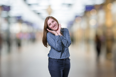 Pretty young businesswoman is happy over blur background.