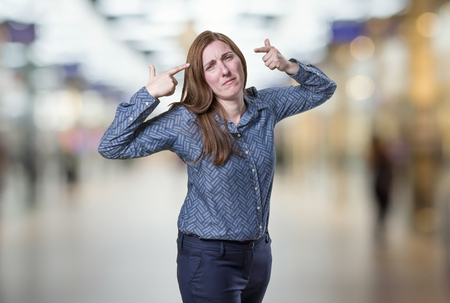 Pretty business woman making suicide gesture over blur background.