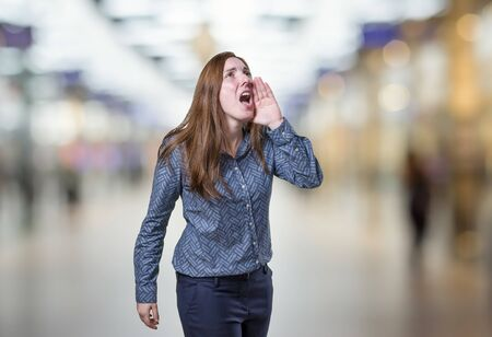 Pretty business woman screaming over blur background.