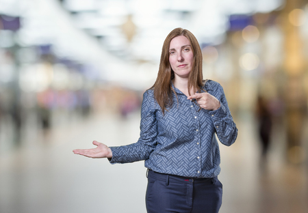 Pretty business woman presenting something over blur background. Stock Photo