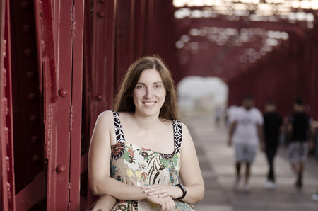 ebro: Beautiful woman standing on a red bridge over Ebro, Spain. Stock Photo