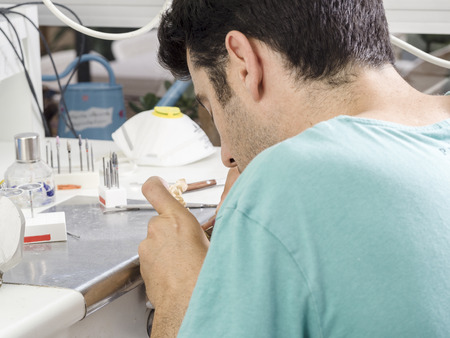 mastication: Dental technician modelling an implant ceramic tooth with a drill.