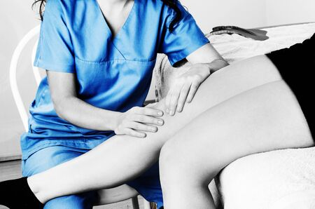 Physiotherapist, chiropractor doing a patellar mobilization, Knee pain in silhouette, color and black and white. Stock Photo