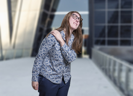 Pretty young happy business woman shoulder pain with glasses