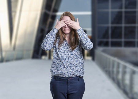 Pretty young business woman covering her eyes