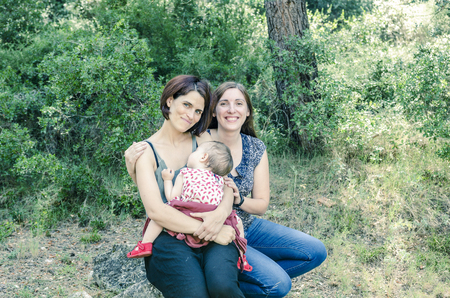Adorable lesbian couple with their baby girl in nature. Stock Photo