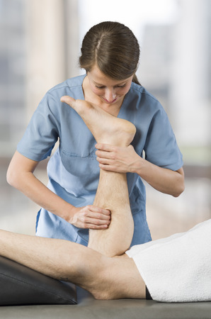 Closeup of hands of chiropractor, physiotherapist doing calf muscle massage to man patient. Osteopathy. Stock Photo