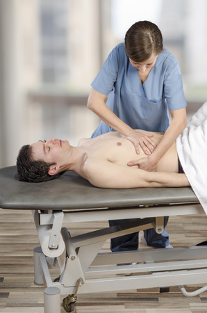 Physiotherapist, chiropractor is doing a liver visceral fascia. Massage to a man patient. Osteopathy