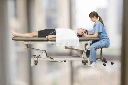 Physiotherapist is doing craniosacral therapy in a stretcher over white background. health care and wellness - massage