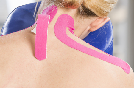 Physiotherapist, chiropractor putting on pink kinesio tape on woman patient. Cervical.