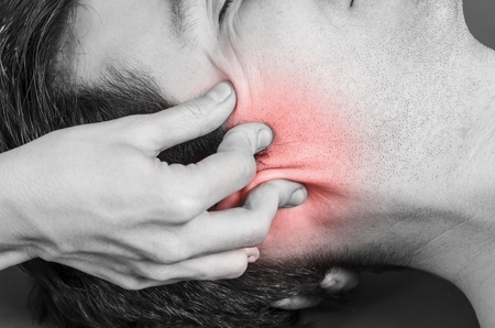 Physiotherapist, chiropractor doing a cranial sacral therapy to a man patient. Activating  trigeminal nerve. Osteopathy