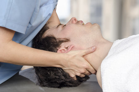Physiotherapist, chiropractor is doing manipulation cervical to a man patient. Osteopathy. Man is screaming of pain