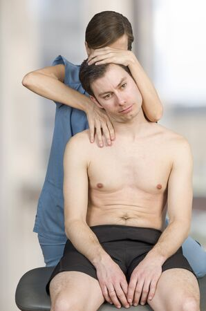 Physiotherapist, chiropractor doing cervical manipulation with axial compression in a clinic.