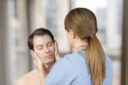 Physiotherapist, chiropractor doing cervical manipulation with rotation in a clinic.