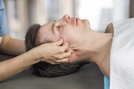 Fysiotherapeut, chiropractor die een craniale sacrale therapie uitvoert bij een mannelijke patiënt. Trigeminuszenuw activeren. Osteopathie Stockfoto