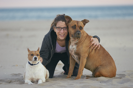 Young woman sitting on the sand with her dogs on a beach.