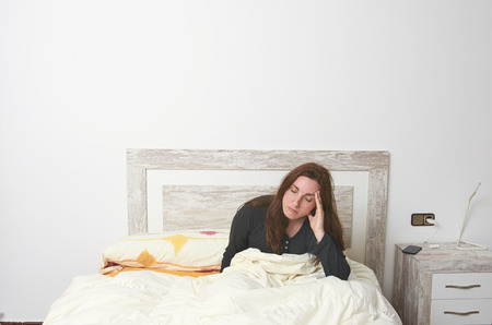 Woman sitting on bed irritated when they hear the alarm clock. Early wake up not getting enough sleep