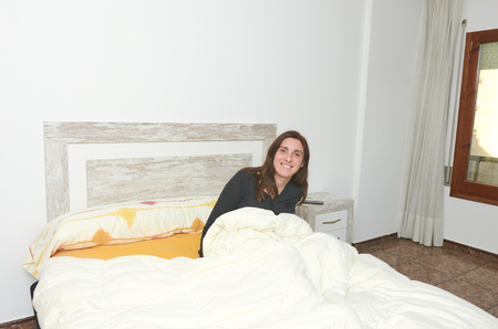 Happy woman smiling on bed after alarm sound
